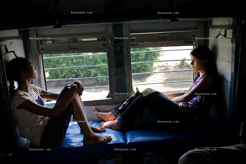 Train passengers on the Himsagar Express 6318 watch the agriculture fields of Punjab pass by on 7th July 2009.. .6318 / Himsagar Express, India's longest single train journey, spanning 3720 kms, going from the mountains (Hima) to the seas (Sagar), from Jammu and Kashmir state of the Indian Himalayas to Kanyakumari, which is the southern most tip of India...Photo by Suzanne Lee / for The National