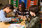 Public elementary school Grade 2 3 students, 2 girls and boy working together on topographical map project using colored modeling clay