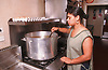 Woman cooking in kitchen using industrial sized saucepan,