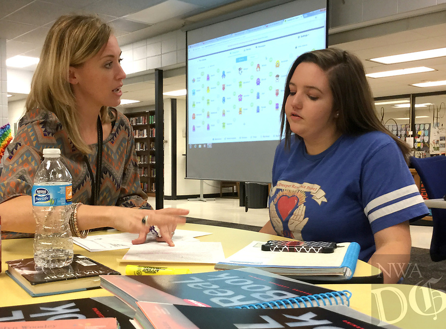NWA Democrat-Gazette/DAVE PEROZEK<br /> English teacher Cristina Cox, left, gives seventh-grader Savannah Robinson, 13, some tips on writing an essay during Thursday's (April 6, 2017) meeting of the after-school program the HUB at Lincoln Junior High School in Bentonville. The HUB, which stands for Helping Understand Better, provides students extra help in literacy and math.