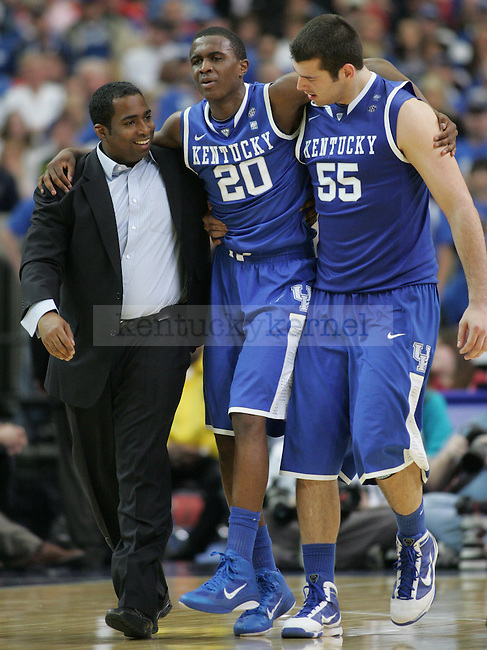 Doron Lamb is carried off of the court by teammate Josh Harrellson and athletic trainer Chris Simmons.  Lamb sustained an injury in the final minutes of the semifinal round of the 2011 SEC Tournament between Kentucky and Alabama, played at the Georgia Dome, Saturday, March 12, 2011.  Photo by Latara Appleby | Staff