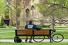 April 27, 2016; A student relaxes on a bench in front of the Main Building. (Photo by Barbara Johnston/University of Notre Dame)