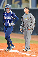 11 February 2012:  FIU Graduate Assistant Coach Francesca Enea coaches from the first base position as the University of Massachusetts Minutewomen defeated the FIU Golden Panthers, 3-1, as part of the COMBAT Classic Tournament at the FIU Softball Complex in Miami, Florida.