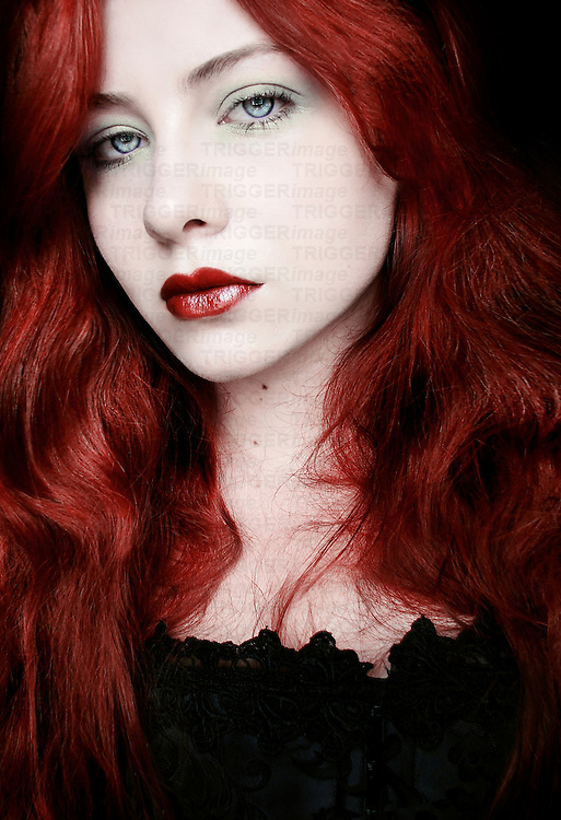 A young woman with red hair looking at the camera