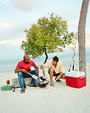 USA, Florida, friends having a beach BBQ, cooking fish, Islamorada