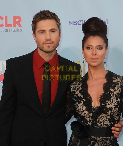 Roselyn Sanchez & Eric Winter.2012 NCLR ALMA Awards - arrivals, held at The Pasadena Civic Auditorium, Pasadena, California USA..16th September 2012.half length black suit red shirt lace dress married husband wife cleavage hair up bun.CAP/ADM/KB.©Kevan Brooks/AdMedia/Capital Pictures.