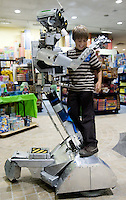 Quebec city, August 1, 2008 - Louis Prevost-Bolduc, 9, takes a ride on a man-sized robot at Benjo toy store on St-Joseph street in Quebec city. Benjo is a 28,000-square-foot game and toy store filled with dolls, teddy bears, crafts, candy, model trains and cars, and more.