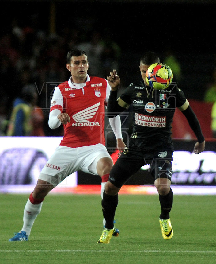 BOGOTA - COLOMBIA -18 -09-2014: Jose de la Cuesta (Izq.) jugador de Independiente Santa Fe disputa el balón con Cesar Arias (Der.) jugador de Once Caldas durante partido entre Independiente Santa Fe y Once Caldas por la fecha15 de la Liga Postobon II-2014, en el estadio Nemesio Camacho El Campin de la ciudad de Bogota. / Jose de la Cuesta (L) playerof Independiente Santa Fe struggles for the ball with  Cesar Arias (R) player of Once Caldas during a match between Independiente Santa Fe and La Equidad for the date 15 of the Liga Postobon II -2014 at the Nemesio Camacho El Campin Stadium in Bogota city, Photo: VizzorImage  / Luis Ramirez / Staff.