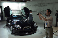 Visitors look at the new Mercedes-Benz SLK at the Auto China 2004 exhibition in Beijing, China..