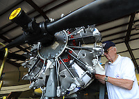 NWA Democrat-Gazette/ANDY SHUPE<br /> Bob Kellett of Bella Vista, a longtime volunteer at the Arkansas Air and Military Museum in Fayetteville, reattaches the exhaust manifold Tuesday, Aug. 18, 2015, on the engine of a Navy SNJ-5 that is being restored at the museum. Volunteers are preparing the plane for painting before it returns to the museum floor to be displayed.