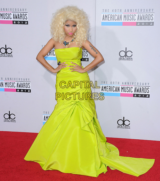 Nicki Minaj.40th Anniversary American Music Awards - Arrivals held at Nokia Theatre L.A. Live, Los Angeles, California, USA..November 18th, 2012.AMA AMAs full length yellow strapless drop waist dress necklace green tattoo hands on hips.CAP/DVS.©DVS/Capital Pictures.