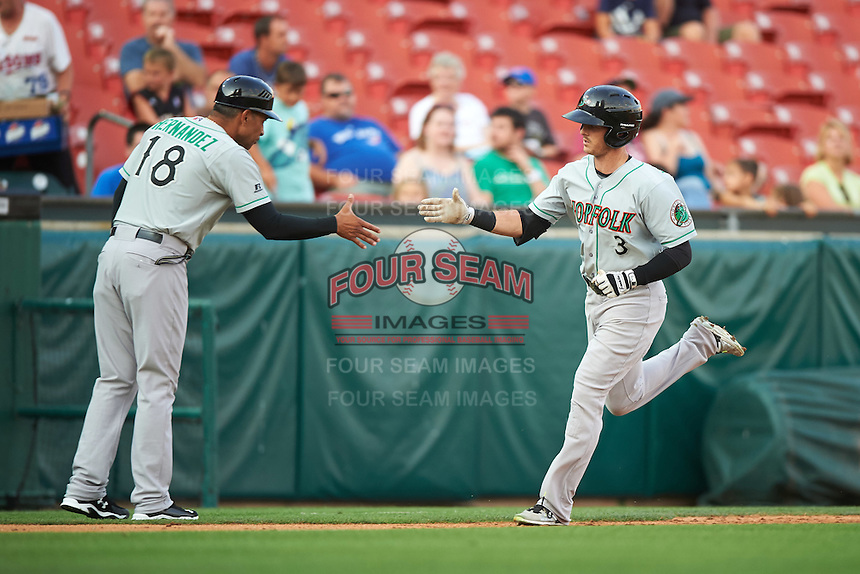 Norfolk Tides coach Jose Hernandez (18) shakes hands with Mike Yastrzemski (3) after a home run during a game against the Buffalo Bisons on July 18, 2016 at Coca-Cola Field in Buffalo, New York.  Norfolk defeated Buffalo 11-8.  (Mike Janes/Four Seam Images)