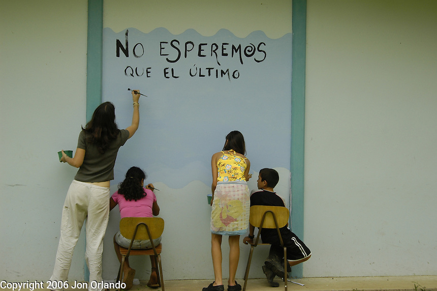 Children at a rural school in Costa Rica paint a mural calling for the protection of the environment on the side of their school.