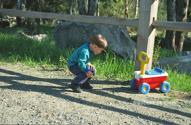 Boy crouching by fence