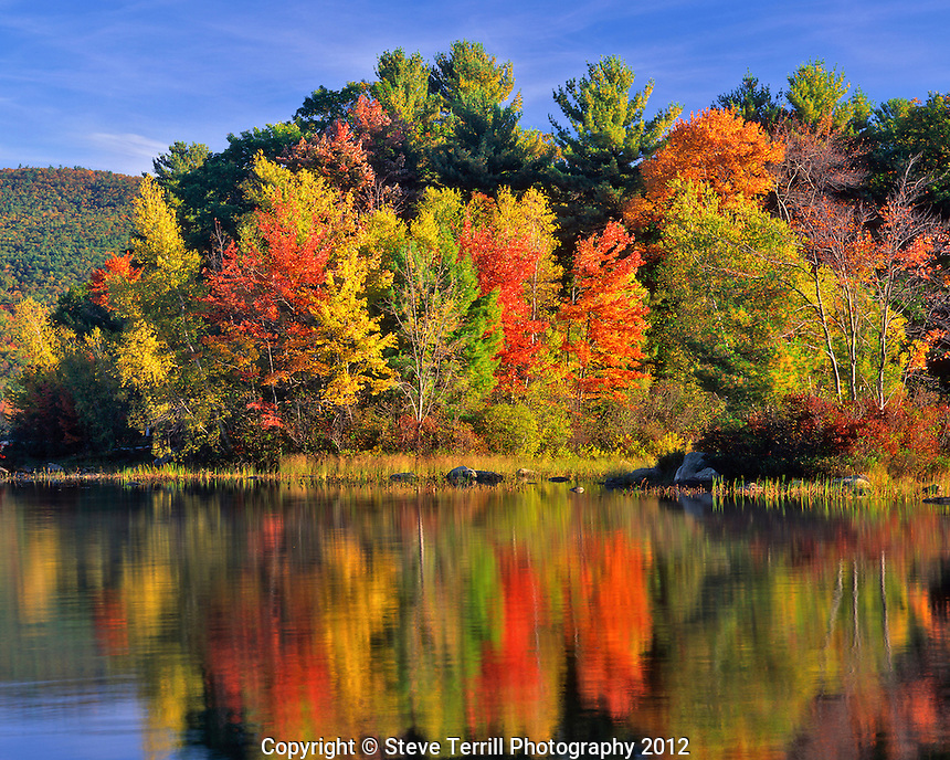 USA, New Hampshire, Trees in fall color reflecting in Lake Kanasatka near Moultonborough.
