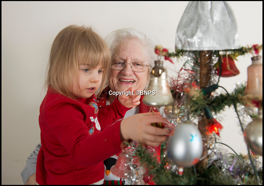 BNPS.co.uk (01202 558833)Pic: LeeMcLean/BNPS<br /> <br /> Sybil Parker (78) with great-granddaughter Bethany Marie Cope (3).<br /> <br /> When it comes to a Christmas tree prudent Derek Parker is the ultimate scrooge - as he's had the same one for 80 years.<br /> <br /> Derek, 80, can't remember a time before the 3ft fragile tree and he's never known Christmas without it.<br /> <br /> His mother Lilly bought it in 1937 when he was three-months-old and after he married wife Sybil 60-years-ago he took it with him.<br /> <br /> The couple, from Crewkerne, bring it out every Christmas for their children, grandchildren and great-grandchildren to enjoy.
