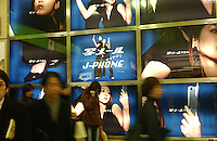 People pass an advertisment for J-phone in a Tokyo subway station in Shibuya, Tokyo. .Mar 2002