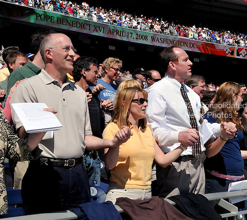 Washington, DC - April 17, 2008 -- Unidentified congregants hold hands in prayer as Pope Benedict XVI celebrates Mass at the new Nationals Park in Washington, D.C. on Thursday, April 17, 2008. This is the first non-baseball event in the park, which opened March 31..Credit: Ron Sachs / CNP.(RESTRICTION: NO New York or New Jersey Newspapers or newspapers within a 75 mile radius of New York City)