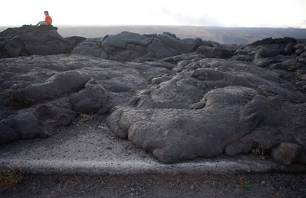 A visitor to Hawaii Volcanoes National Park, sits atop lava which flowed over a former park highway. The park is made up of over 300,000 acres of land, stretching from sea level to the summit of Mauna Loa. Photo by Kevin J. Miyazaki/Redux