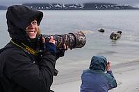 Polar traveller Liisa Widstrand photographing walrus, Odobenus rosmarus, Svalbard, Norway, Arctic ecotourism