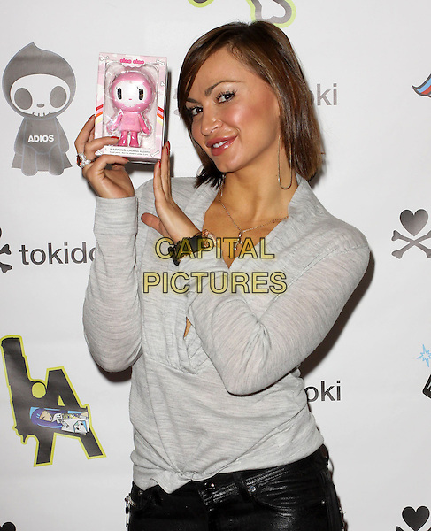 KARINA SMIRNOFF.Visits Gifting Services Inc held At El Gifting Services Showroom,  West Hollywood, California, USA, .24th April 2010..**EXCLUSIVE ALL ROUNDER**.half length grey gray top holding product cowel neck jumper sweater .CAP/ADM/FS.©Faye Sadou/AdMedia/Capital Pictures.