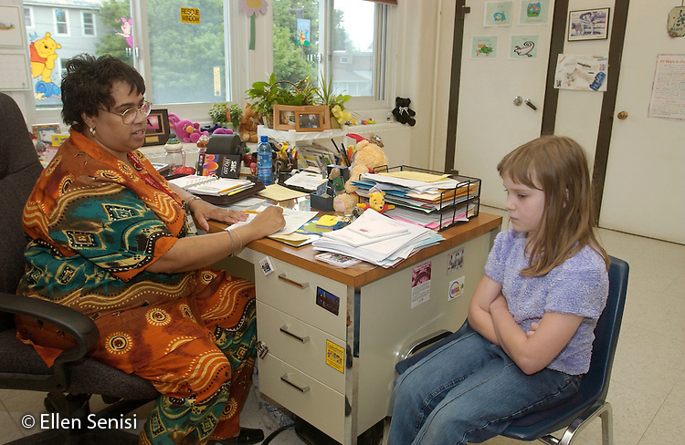 MR / Schenectady, NY.Yates Arts-in-Education Magnet School (urban school, arts theme school).Student (girl, age 8, Grade 3) called to principal's office after causing problem in school..Principal (Native American and African-American, age 42) is writing up a Discipline Referral Form. Consequences increase each time one is written up for a student in a particular period of time..MR: Sco4 Koe2.© Ellen B. Senisi