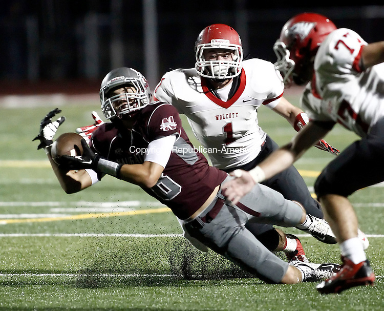 Naugatuck, CT- 20 September 2013-092013CM12-    Naugatuck's Rick Plasky dives for a catch as Wolcott's #1 Adam Santopietro and #77 Zachary Burksa  move in to secure the tackle during their NVL matchup in Naugatuck Friday night.    Christopher Massa Republican-American