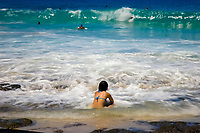 Japanese visitor, breaking wave and bodyboarders during large surf at Magic sands beach, Kailua Kona The Big Island of Hawaii