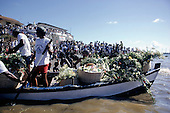 Salvador, Brazil. Boat laden with flowers being rowed out to sea; crowds of people look on; Festa de Iemanja, Bahia State.