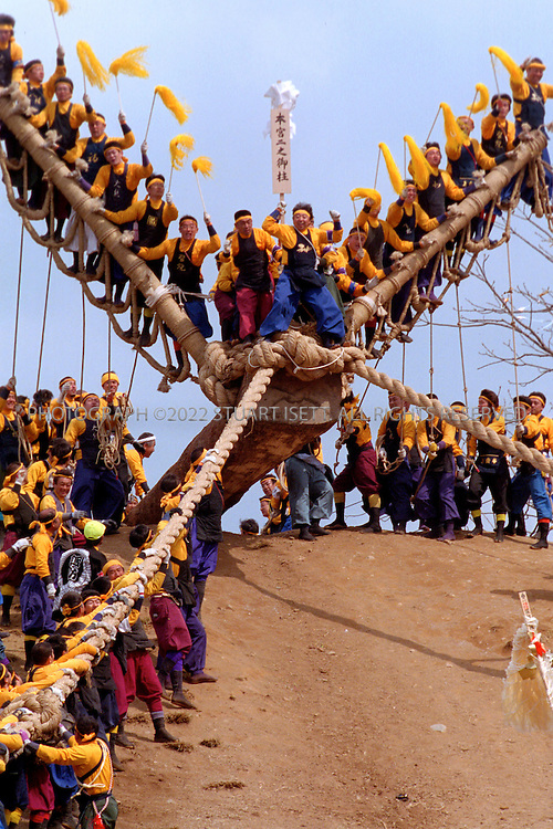 """4/2/2004--Suwa, Japan..Members of a log team wait at the top of the hill on their log as the prepare slide down the hill during the Onbashira Festval in Suwa, Japan...The basic purpose of the 1200 year old Onbashira Festival is rooted in Shinto, the indigenous religion of Japan. In the Shinto way of thinking, the Gods, or kami, are living in the natural environment which surrounds human beings. The Onbashira Festival serves as a reminder of the importance of nature to human beings: large fir trees (symbolic """"gods"""") are brought down from the mountains, carried into town and set to stand at the outskirts of the Suwa Grand Shrine. In this way, the people of the Suwa region never completely lose their contact with nature and the gods, and they renew this contact at least once every 6 years through Onbashira Festival..Photograph by Stuart Isett.©2004 Stuart Isett. All rights reserved"""