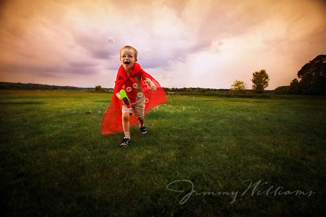 A little boy with a Superman cape on runs through the field with a bubble gun.