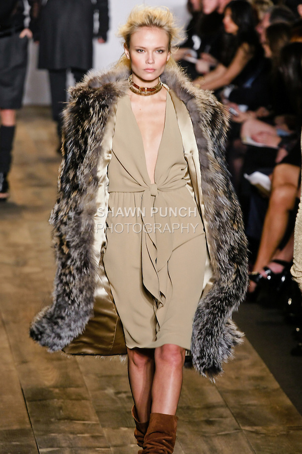 Natasha Poly walks the runway in a shredded cross fox anorak coat, and camel marocaine scarf dress at the Michael Kors Fall 2010 runway fashion show, during Mercedes-Benz Fashion Week Fall 2010.