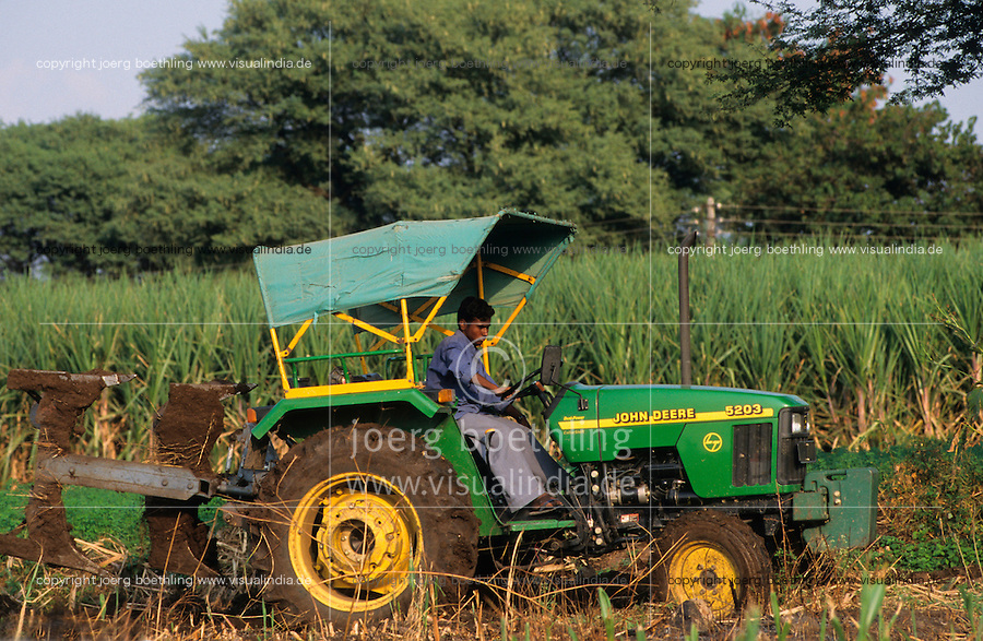 INDIA Maharashtra, farmer plows field with John Deere tractor, background sugarcane field / INDIEN, Landwirt pfluegt sein Feld mit John Deere Traktor, Hintergrund Zuckerrohr