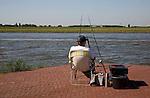 Man sitting alone fishing in the River Maas at Ablasserdam, Netherlands