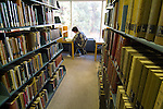 Young male college student studying in a library