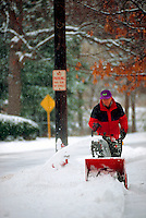 Man clearing snow using a snowblower.
