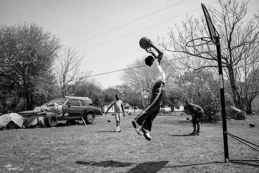 Three young Gullah children play basketball in the backyard of a home in the community of Sol Legare on James Island near Charleston, SC.
