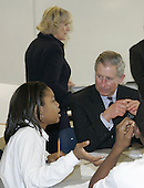 Washington, D.C. - November 2, 2005 -- Prince Charles talks with a student as his wife Camilla, the Dutchess of Cornwall, walks around the classroom during a visit the SEED School in Washington, Wednesday, Nov. 2, 2005. The SEED School offers an intensive academic and boarding education to 320 urban children in grades seven through twelve. Prince Charles and Camilla are on an 8-day tour of the United States. .Credit: AP Photo/Susan Walsh via CNP.(Restriction: No New York Metro or other Newspapers within a 75 mile radius of New York City)