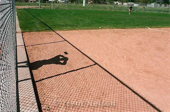 Spectator's shadow and outfielder at Skyline vs Hillcrest high school softball, second round of the state tournament.<br />