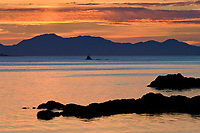 Commercial fishing boat travels through the Tongass Narrows at sunset, southeast, Alaska.