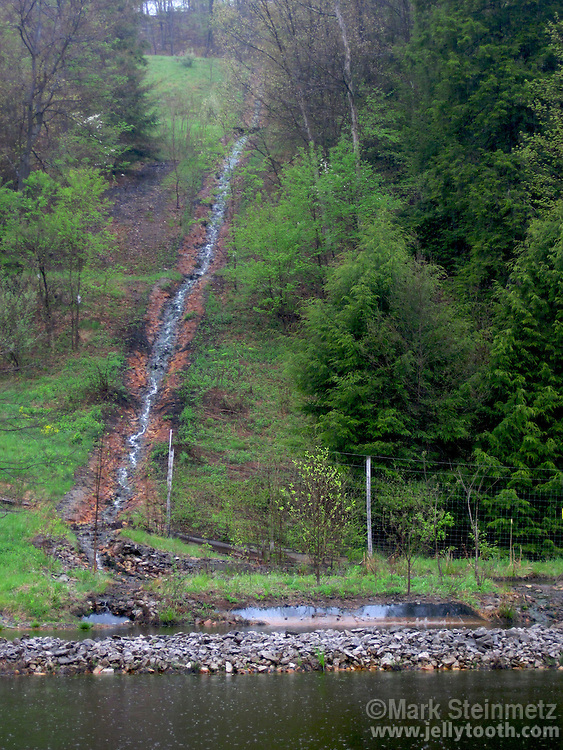 A low cost, low tech solution is being employed in Preston County, West Virginia to remediate effects of Acid Mine Drainage (AMD) on Muddy Creek in the Cheat River watershed.  Highly acidic and metal laden AMD water is diverted down the hillside in limestone grouted channels to neutralize the acidity. The water falls into a series of settling ponds, in which many of the heavy metals fall out. The flow then is returned to the creek by another limestone channel. April 2010, West Virginia, USA.