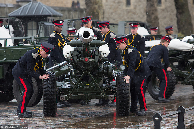 Members of the Honourable Artillery Company (HAC) wheel in light guns during a rain shower ahead of a 62 Gun Salute in honour of Her Majesty the Queen's 88th birthday today, 21st April 2014 at the Tower of London in front of Tower Bridge in London.