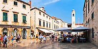 Panoramic photo of Stradun, Dubrovnik, Dalmatia, Croatia. This is a panoramic photo of tourists in a cafe in front of the City Bell Tower, aka the clock tower on Stradun, the most famous street in Dubrovnik. Stradun is the centre of cafe culture in Dubrovnik with many cafes along its cobbled length.