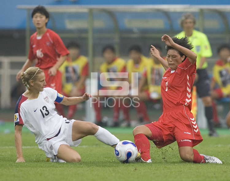 Ho Sun Hui of North Korea and Kristine Lilly (13) of the USA go for the ball.  The United States (USA) and North Korea (PRK) played to a 2-2 tie during a FIFA Women's World Cup China 2007 opening round Group B match at Chengdu Sports Center Stadium, Chengdu, China, on September 11, 2007.