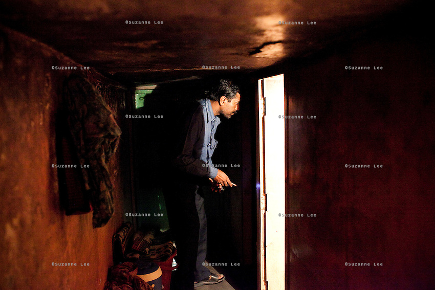 Mr. Pathak looks through rooms in a brothel as he goes from brothel to brothel with policemen in search of his daughter on 28th September 2010, on GB Road, Delhi's red light district, India..Mr. Kailash Pathak, a Hindu priest, has travelled to Delhi from his village in New Jalpaiguri, West Bengal, to look for his missing daughter, Khushbu Pathak aged 13, who was last seen in the custody of his neighbours in February this year and believed to have been sold to brothels in the capital, Delhi. The accused neighbours have since been arrested in Delhi but the girl is yet to be found. Photo by Suzanne Lee
