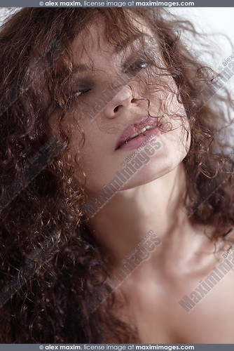 Natural close-up beauty portrait of a young woman with long curly brown hair partially covering her beautiful face