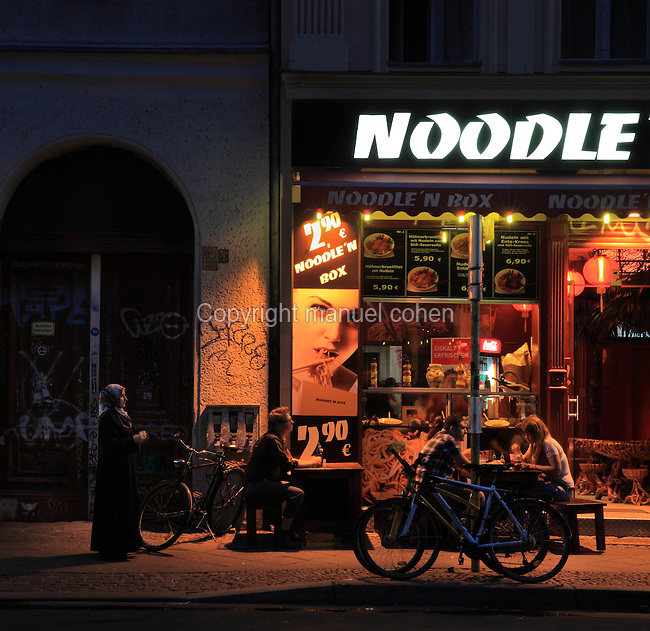 People eating outside a noodle bar at night on Oranienstrasse, Berlin, Germany. Picture by Manuel Cohen