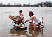 Hoog water in Deventer. Twee jongens ontbijten op de overstroomde kade