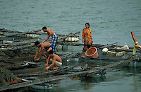 Villagers feeding fish in aquaculture cages