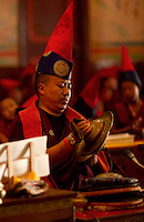Buddhist monks chanting prayers from scrolls during the Losar New Year ceremony inside a monastery in the Himalayan foothills of Sikkim, India